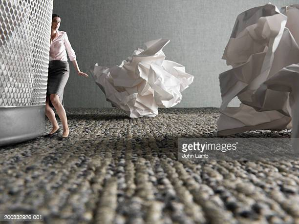 Minature businesswoman by giant rubbish bin (digital composite)