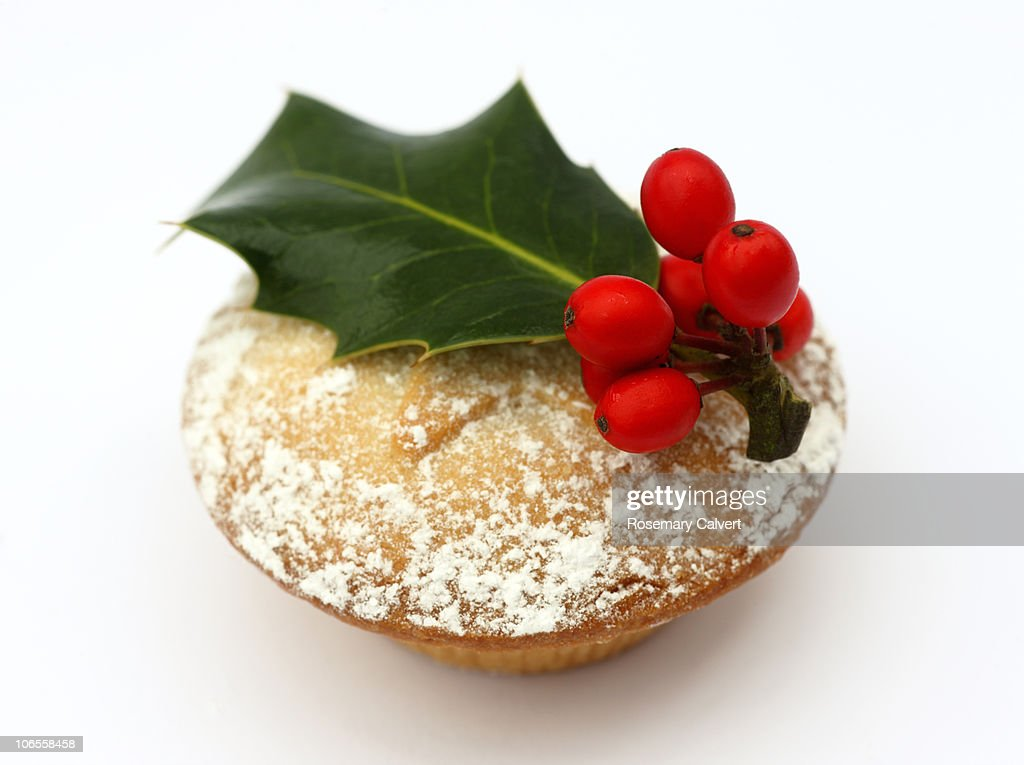 Mince pie topped with holly leaf and red berries.