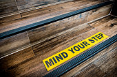 Mind your step sticker sign pasted on wooden stair. Warnings, abstract, or indoor architecture concept
