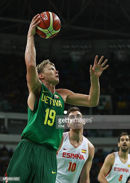Mindaugas Kuzminskas of Lithuania goes to the basket against Victor Claver and Jose Calderon of Spain during the Men's Preliminary Round Group B...