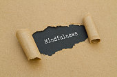 Mindfulness word written under torn paper.