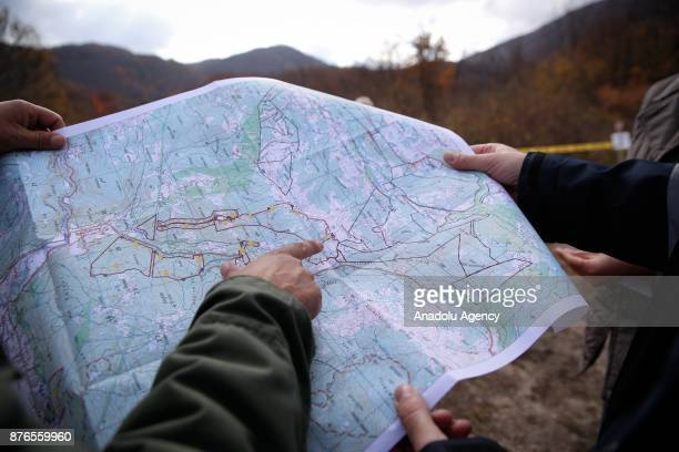 Mine clearance experts examine a map at a woodland in Sarajevo Bosnia and Herzegovina on November 20 2017 22 years after the signing of the Dayton...