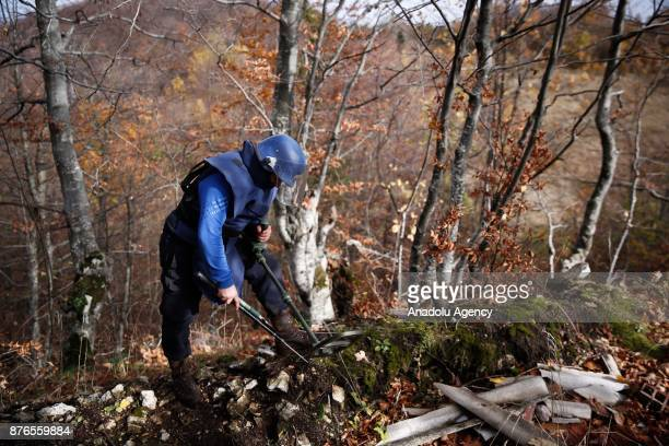 Mine clearance experts search for unexploded mines at a woodland in Sarajevo Bosnia and Herzegovina on November 20 2017 22 years after the signing of...