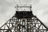 A large gun metal steel structure with cables run over guiding wheels at the top, cloudy background. Precious metals extraction.