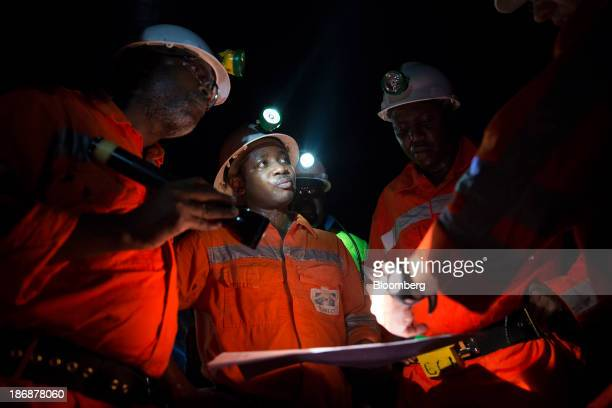 Mine managers use flashlights to check notes during an inspection of the underground operations at the Gara gold mine operated by Randgold Resources...