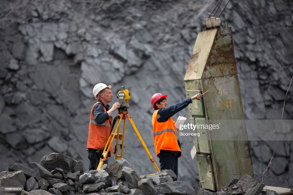 Mine surveyors work in the open pit of the Lebedinsky GOK (LGOK) iron ore mining and processing plant, operated by Metalloinvest Holding Co., in Gubkin, Russia, on Tuesday, May 28, 2013. Lebedinsky, Russia's third biggest iron ore mine, is owned 81 percent owned by Russian billionaire Alisher Usmanov, who also owns Mikhailovsky GOK, Russia's second-biggest iron ore mine, and Oskol Electrometallurgical Combine, a steel plant supplied by Lebedinsky. Photographer: Andrey Rudakov/Bloomberg via Getty Images