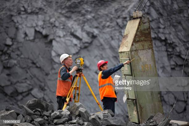 Mine surveyors work in the open pit of the Lebedinsky GOK iron ore mining and processing plant operated by Metalloinvest Holding Co in Gubkin Russia...