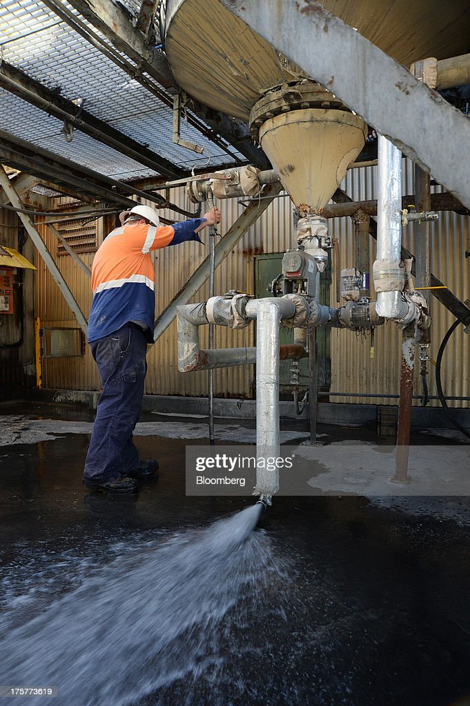 A mine worker adjusts the water pressure under an elution tank at the Norton Gold Fields Ltd. Paddington operations 35 kilometers north-west of Kalgoorlie, Australia, on Wednesday, Aug. 7, 2013. Norton, the Australian producer controlled by China's Zijin Mining Group Co., is seeking further acquisition targets as falling prices cut the value of mines. Photographer: Carla Gottgens/Bloomberg via Getty Images