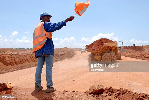 A mine worker directs trucks carrying ore from a quarry at Metorex's Ruashi copper mine near Lubumbashi Democratic Republic of Congo on Friday Feb 8...