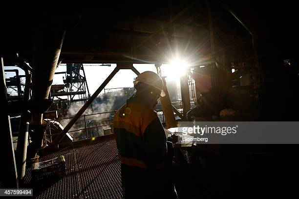 A mine worker inspects notes during operations in the refining and processing plant at the Kibali gold mine operated by Randgold Resources Ltd in...