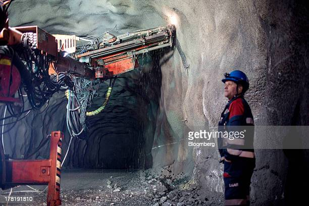 A mine worker observes drilling equipment inside the underground iron ore mine operated by LKAB Sweden's stateowned mining company in Kiruna Sweden...