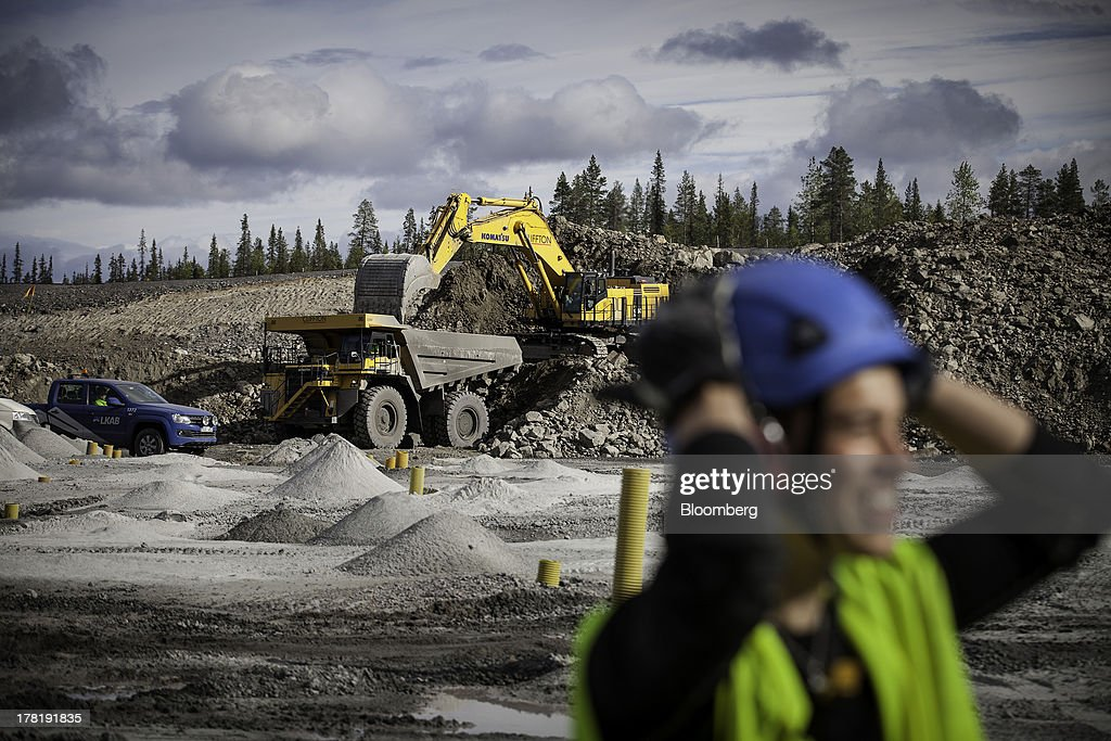 A mine worker stands beyond an excavator removing waste rock from a site at the open cast iron ore mine run by LKAB, Sweden's state-owned mining company, in Svappavaara near Kiruna, Sweden, on Thursday, Aug. 22, 2013. Swedes living in the Arctic town of Kiruna are packing up their belongings before their homes are bulldozed to make way for iron ore mining driven by Chinese demand. Photographer: Casper Hedberg/Bloomberg via Getty Images
