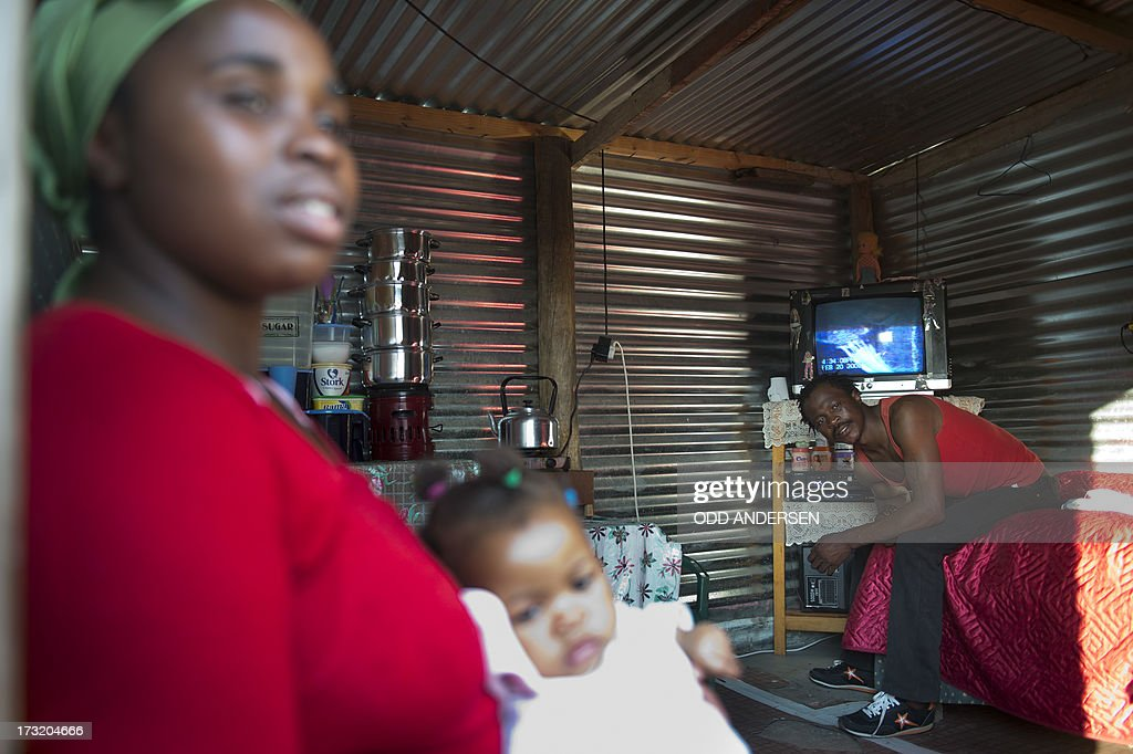 A miner and his family are seen in their shack on July 9, 2013 in the Nkaneng shantytown next to the platinum mine, run by British company Lonmin, in Marikana. On August 16, 2012, police at the Marikana mine open fire on striking workers, killing 34 and injuring 78, during a strike was for better wages and living conditions. Miners still live in dire conditions despite a small wage increase. AFP PHOTO / ODD ANDERSEN