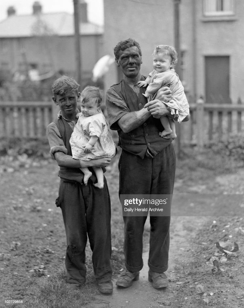 A miner and his family, Rhondda Valley, South Wales, 22nd June 1931. 'The boys in a mining village are usually only too eager to join their fathers in the pit. They go down as soon as they are old enough to work.' Photograph taken by James Jarche of the Daily Herald newspaper for a series of articles called 'In Search of Wales' written by H V Morton in 1934. The pictures included the first flash photographs taken underground, which involved a considerable risk of an explosion. The articles were later published together in a book of the same name.