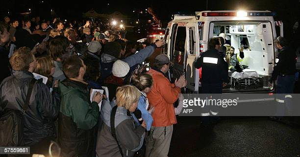 Miner Brant Webb waves from the back of an ambulance as he passes by media and local residents after spending two weeks trapped nearly a kilometer...
