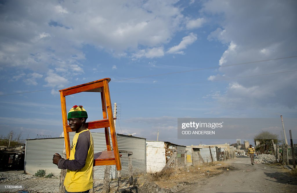 A miner carries a table on July 9, 2013 in the Nkaneng shantytown next to the platinum mine, run by British company Lonmin, in Marikana. On August 16, 2012, police at the Marikana mine open fire on striking workers, killing 34 and injuring 78, during a strike was for better wages and living conditions. Miners still live in dire conditions despite a small wage increase.