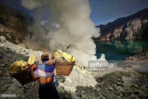 A miner carries sulfur during an annual offering ceremony on the Ijen volcano on December 17 2013 in Banyuwangi Indonesia The ritual is performed by...