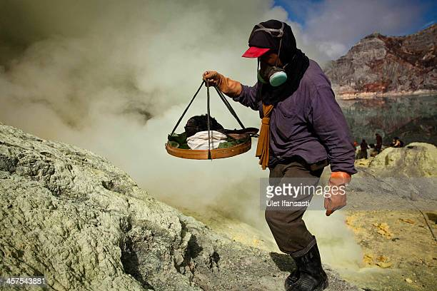 A miner carry a goats head for burial in the crater as part of an annual offering ceremony on the Ijen volcano on December 17 2013 in Banyuwangi...
