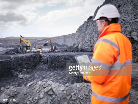 Miner checks plans on digital tablet in surface coal mine
