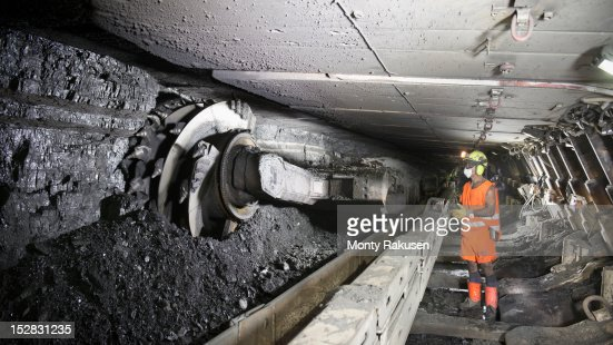 Miner cutting coal at coal seem in deep mine : Stock Photo