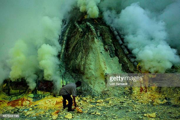 A miner extracts sulphur from pipe at the flow crater during an annual offering ceremony on the Ijen volcano on December 17 2013 in Banyuwangi...