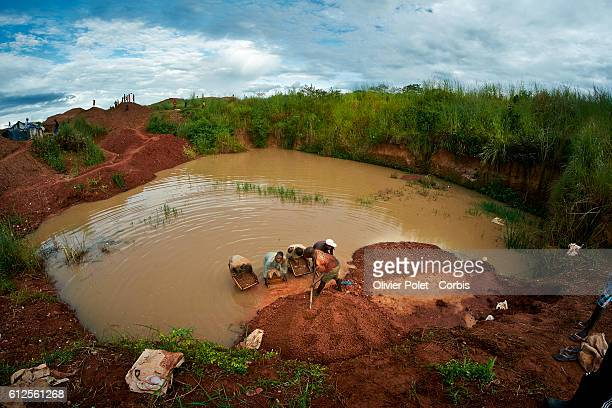 A miner fills the rich earth in the sifting frames held by his colleagues 28 March 2013 in search of a diamond gem near an Angolan village not far...