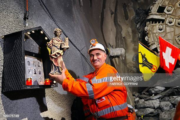 A miner holds an effigy of St Barbara patron saint of miners after a giant drilling machine completed the world's longest tunnel beneath the Swiss...