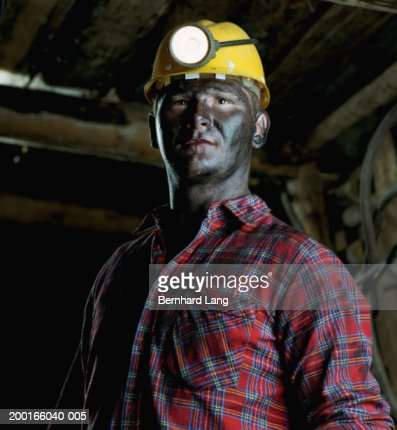 Miner in mine shaft wearing hard hat and headlamp