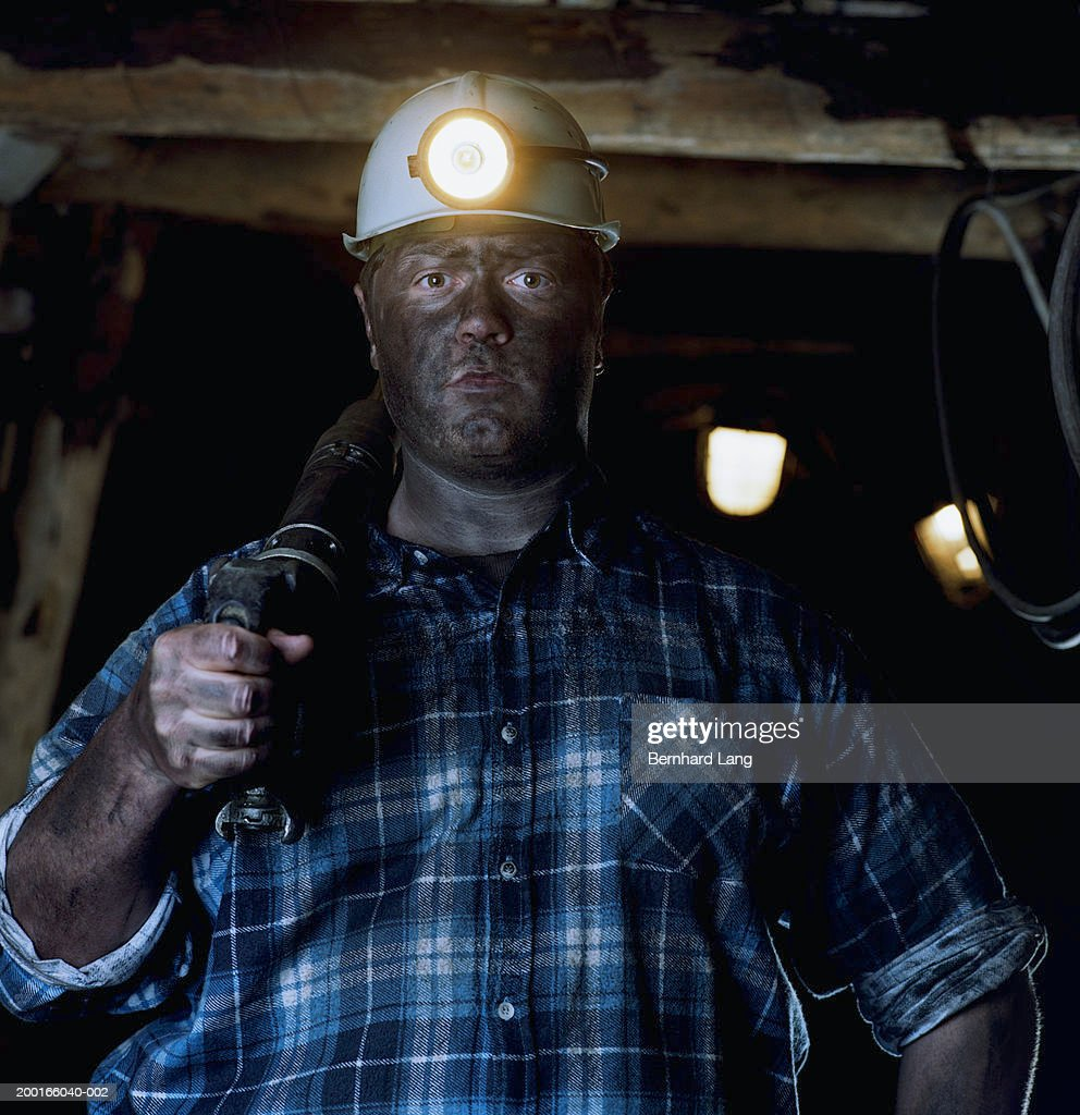 Miner in mine shaft with drill over shoulder, portrait : Stock Photo