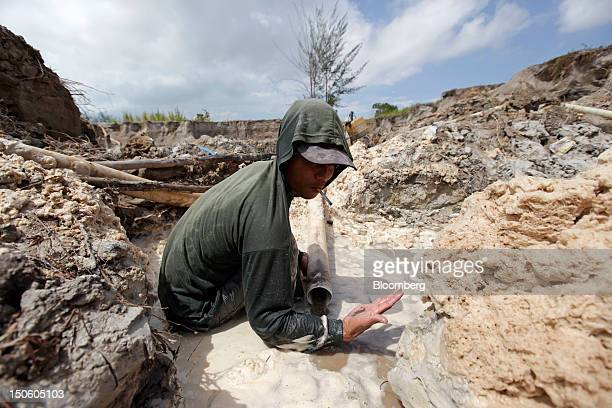 A miner inspects the quality of ore in a tinmining pit in Sungai Liat Bangka Island Indonesia on Saturday July 28 2012 In recent years about onethird...