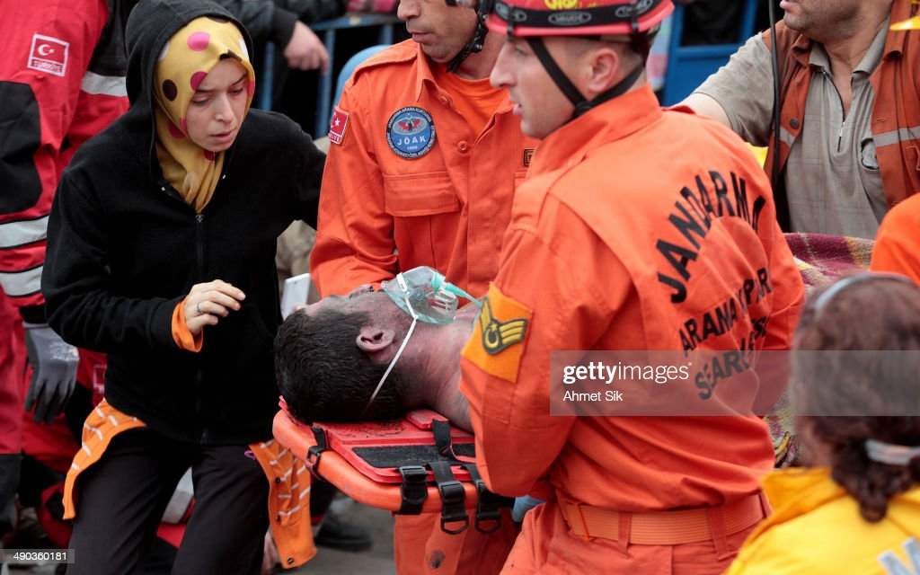 A miner is carried to an ambulance as his relative looks concerned on May 14 2014 in Soma Turkey Rescuers pulled more dead and injured from the coal...