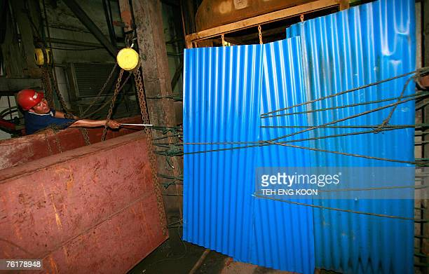 A miner is seen near a mine opening covered with blue corrugated sheets as the mine rescue operation continues at a coal mine in Xintai eastern...