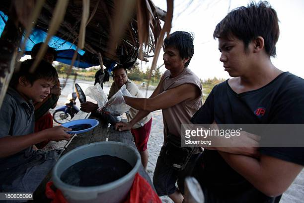 A miner left sells tin ore to buyers in Sungai Liat Bangka Island Indonesia on Friday July 27 2012 In recent years about onethird of all the tin...