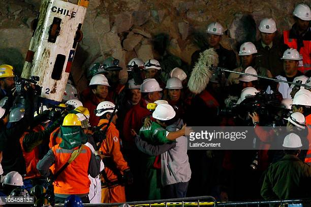 Miner Luis Urzua is embraced by his brother after being sucessfuly lifted to the surface during the rescue operation of 33 miners trapped 700 meters...
