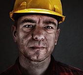 Portrait of a miner with yellow helmet against dark background.