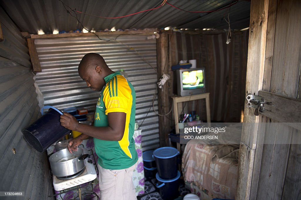 A miner prepares food in his shack on July 9, 2013 in the Nkaneng shantytown next to the platinum mine, run by British company Lonmin, in Marikana. On August 16, 2012, police at the Marikana mine open fire on striking workers, killing 34 and injuring 78, during a strike was for better wages and living conditions. Miners still live in dire conditions despite a small wage increase.