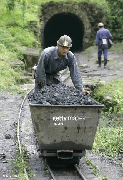 A miner pushes a cart containing coal out from a mine in Qianwei county in China's southwestern province of Sichuan 25 May 2005 Demand for coal in...