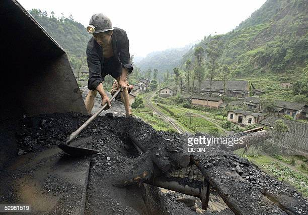 STORY 'CHINAECONOMYENERGYCOALINVESTMENT' A miner shovels coal at a mine in Qianwei county in China's southwestern province of Sichuan 25 May 2005...