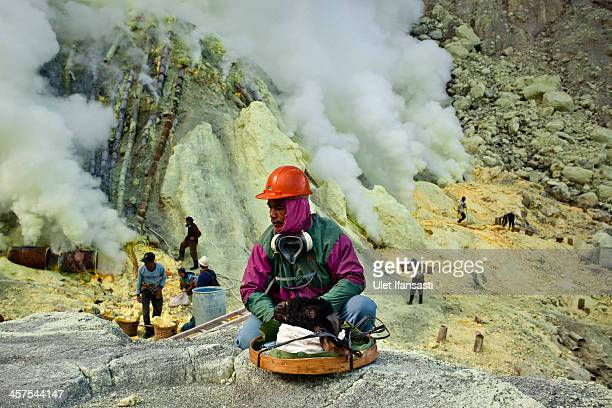 A miner sits beside a goat head as he prepares for its burial in the crater as part of an annual offering ceremony on the Ijen volcano on December 17...