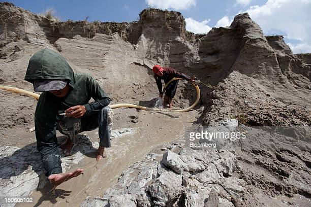 A miner sprays water over a tinmining pit to create a slurry for sluicing tin ore as another inspects the quality of the ore in Sungai Liat Bangka...