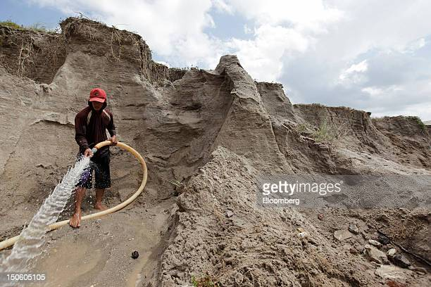 A miner sprays water over a tinmining pit to create a slurry for sluicing tin ore in Sungai Liat Bangka Island Indonesia on Saturday July 28 2012 In...