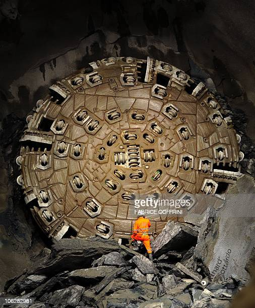 A miner stands in front of a giant drilling machine that completed the world's longest tunnel beneath the Swiss Alps during a ceremony on October 15...