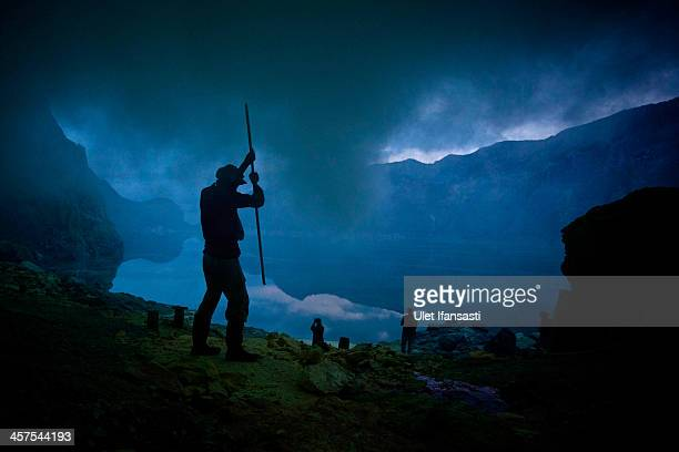 A miner uses a pole to extract sulphur from a pipe at the flow crater during an annual offering ceremony on the Ijen volcano on December 17 2013 in...