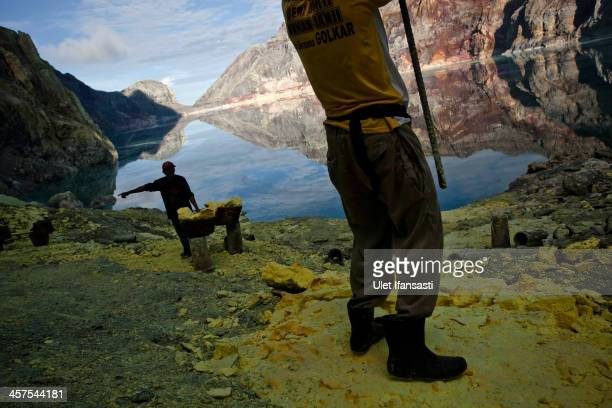 A miner uses a pole to extract sulphur from pipe at the flow crater during an annual offering ceremony on the Ijen volcano on December 17 2013 in...