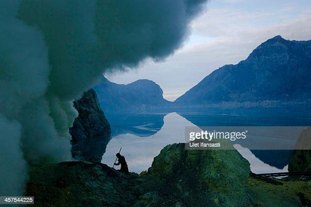 A miner uses a pole to extract sulphur from pipes at the flow crater during an annual offering ceremony on the Ijen volcano on December 17 2013 in...
