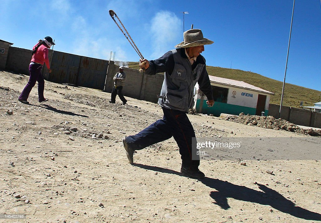 A miner uses a slingshot against policemen during a violent rally protesting against Swiss-owned mining company Xstrata, in the Cuzco province of Espinar, 1,100 kms southeast of Lima. At least two people were killed during clashes, after hundreds of demonstrators lugged tree trunks and boulders into roads in the Espinar area of Cusco, in southern Peru, to protest what they say is the mining firm's pollution of the Salado and Canipia Rivers.