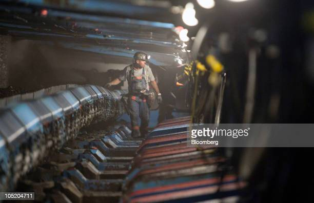 A miner walks under hydraulic jacks next to a coal seam in Foresight Energy LLC's Pond Creek longwall coal mine in Johnson City Illinois US on Monday...