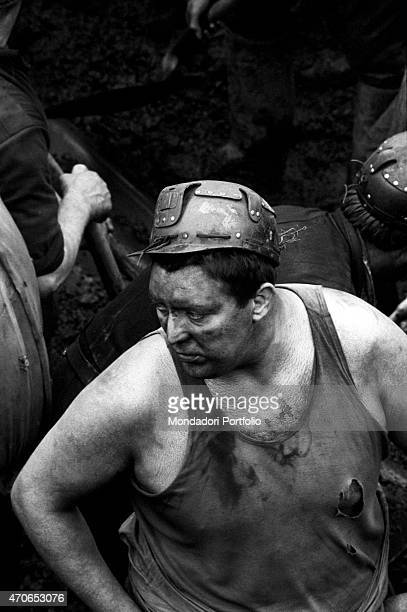 'A miner wearing a safety helmet in a vest and filthy with mud at work together with some colleagues on the deep layer of silt and debris after a...