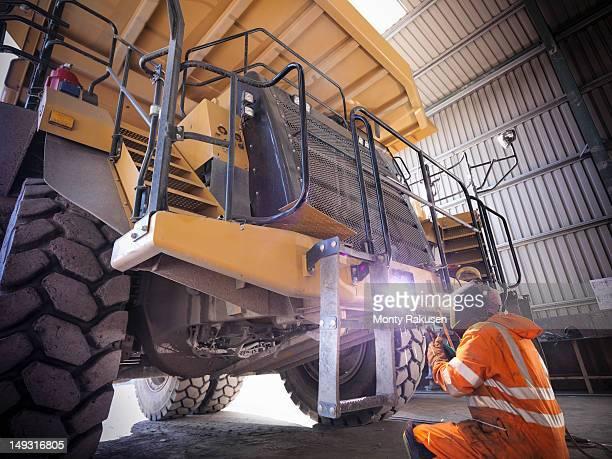 Miner welding dumper truck in opencast coalmine