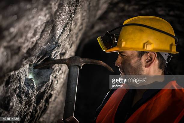Miner working at a mine using a pick